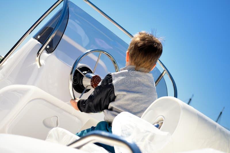 Marin de petit enfant orientant un voilier comme capitaine photographie stock libre de droits