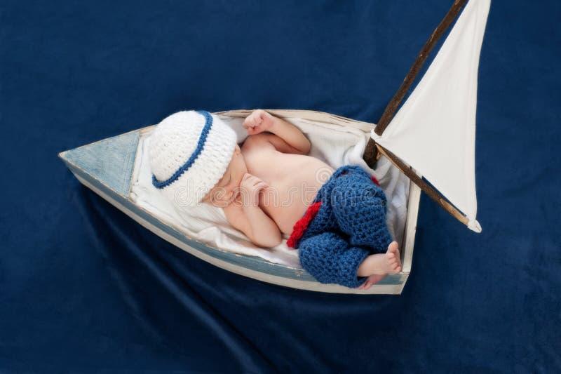 Marin nouveau-né Sleeping de bébé garçon dans un bateau photographie stock
