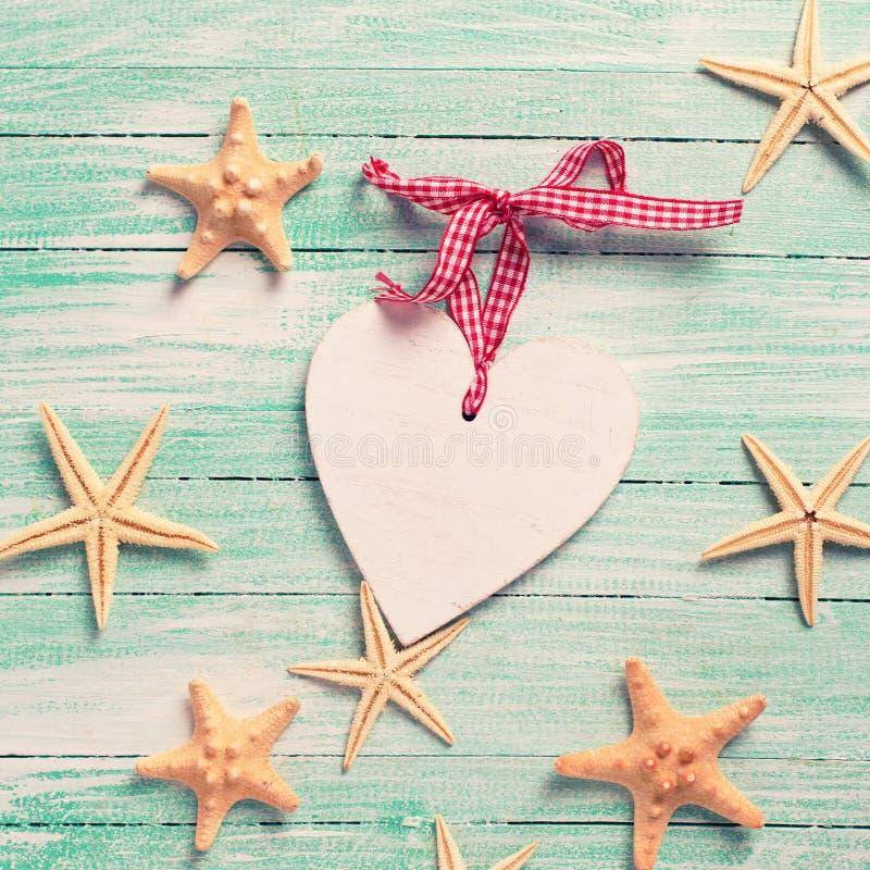 Marin- objekt (havsstjärnor) och dekorativ hjärta på turkos wo royaltyfria bilder