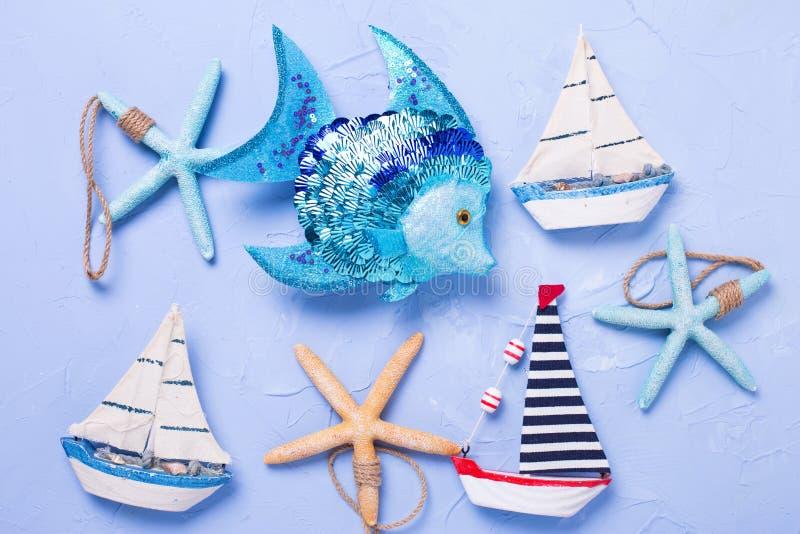 Marin- objekt och dekorativa träleksakfartyg på texturerade blått royaltyfria bilder