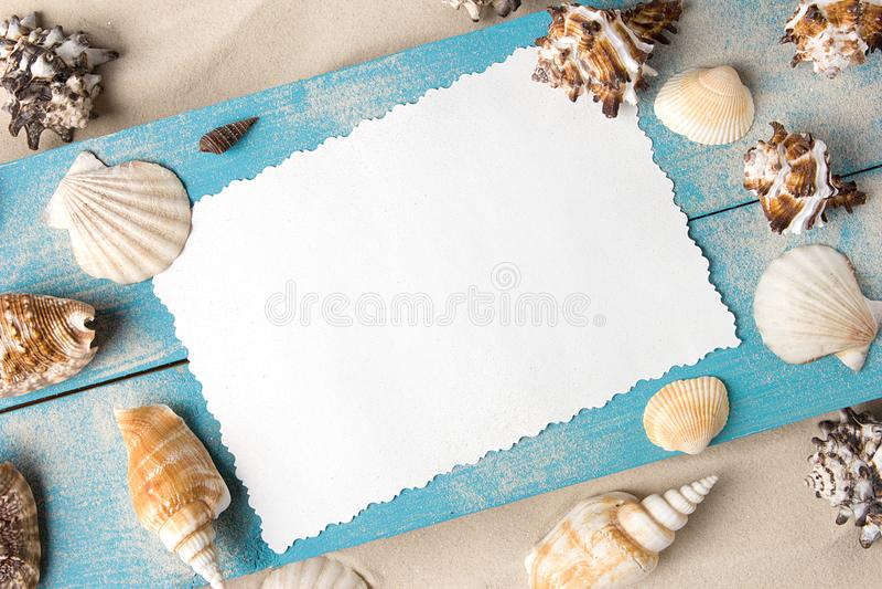 Marin- sommarvykort Snäckskal på blåa träbräden i sanden på stranden arkivfoto