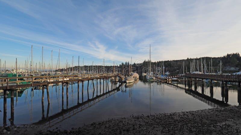 Marina on Bainbridge Island off Seattle, Washington on calm sunny winter afternoon. Bainbridge Island, Washington - February 10, 2018 - Marina on tranquil sunny stock photos