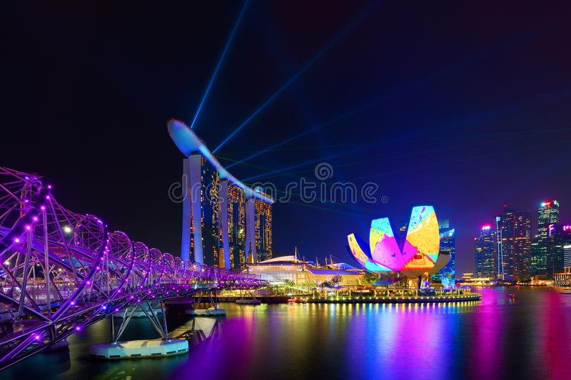 Marina Bay Sands and Helix bridge with laser shows in Downtown Singapore city in Bay area. Financial district and skyscraper. Buildings at night royalty free stock photography