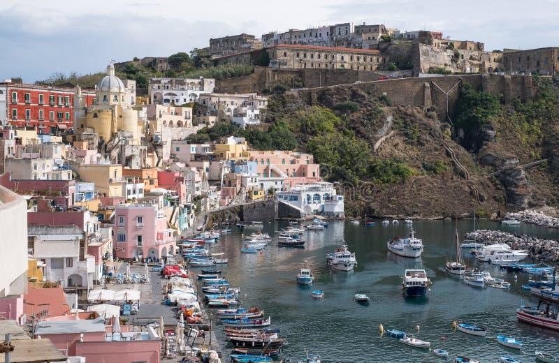 Marina Corricella Italien, fiskeläge på ön av Procida med pastellfärgade färgade hus som dråsar ner klippan till sen royaltyfri foto