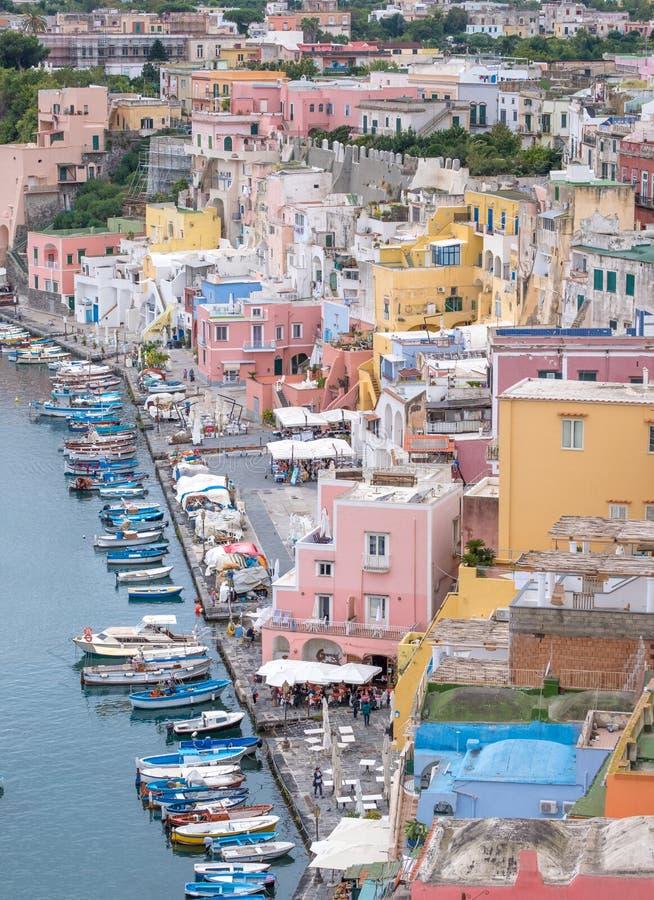 Marina Corricella Italien, fiskeläge på ön av Procida med pastellfärgade färgade hus som dråsar ner klippan till sen royaltyfri fotografi