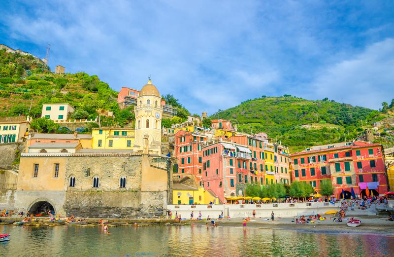 Marina harbor, Chiesa di Santa Margherita di Antiochia church, green hill and colorful buildings houses in Vernazza. Village, blue sky background, National park royalty free stock photo