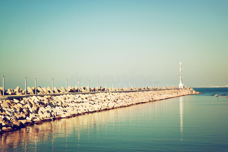 Marina with the lighthouse and the sea. vintage filtered image stock photo