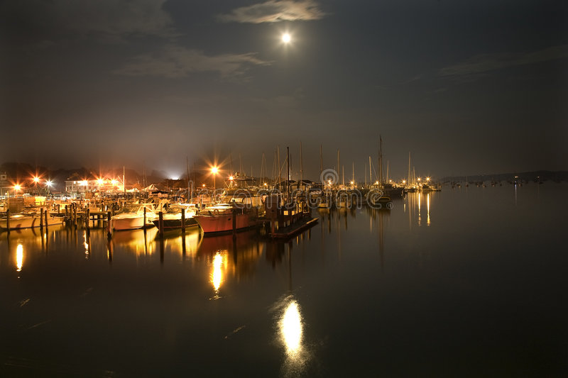 Marina at night. Yachts moored at night in an illuminated harbor with moonlight reflected on the ocean royalty free stock photo