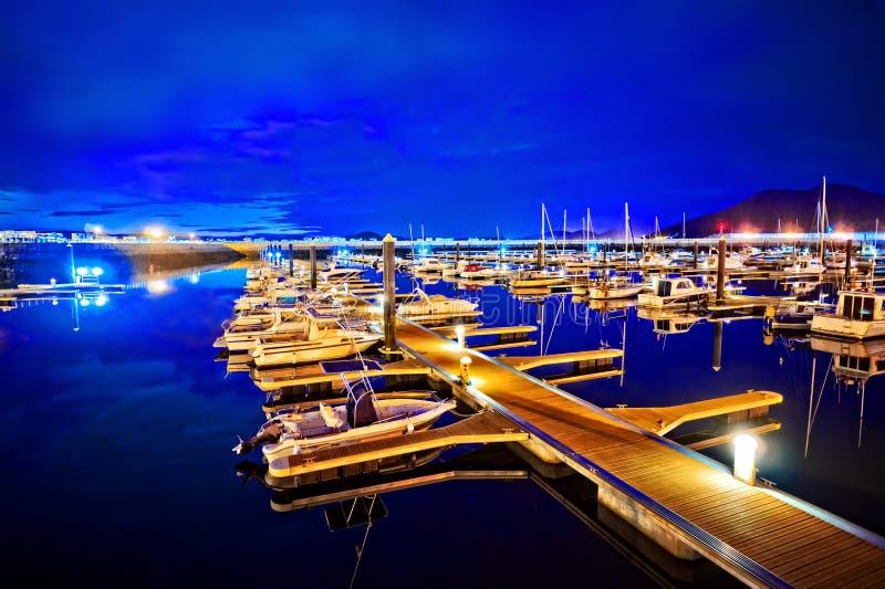 Marina på natten med förtöjde yachter royaltyfri fotografi