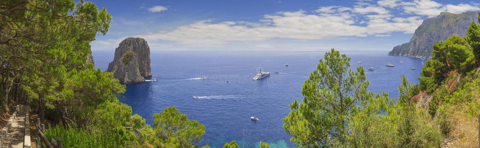 Panoramic view of famous Faraglioni Rocks and Marina Piccola in Capri island, Italy. Typical panoramic pedestrian path of Capri. Marina Piccola. Boats and stock photo