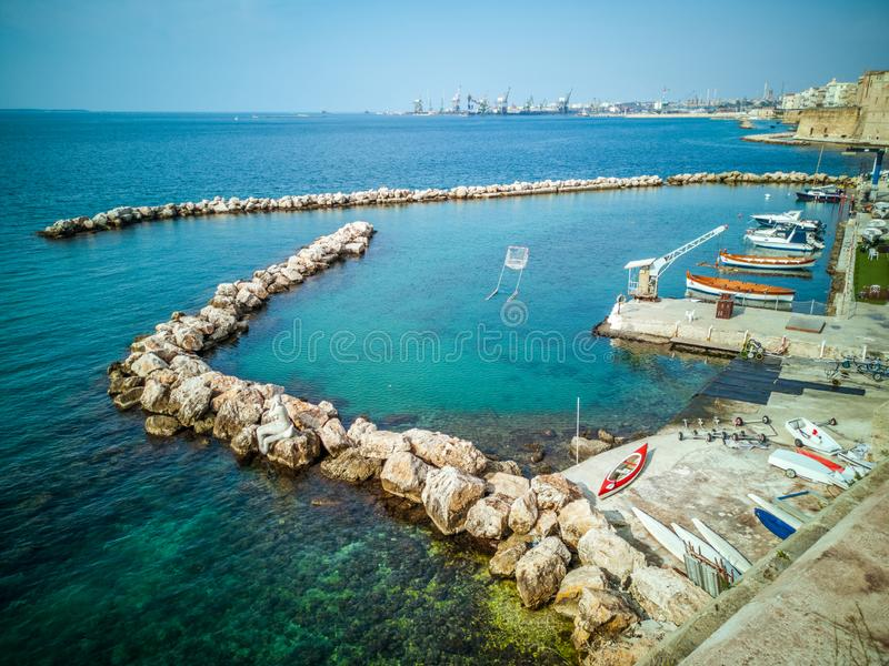 Marina with small boats on the coast on the seafront of Taranto in Italy. Reef, blue sea and in the distance The Castello Aragonese fortification royalty free stock photos
