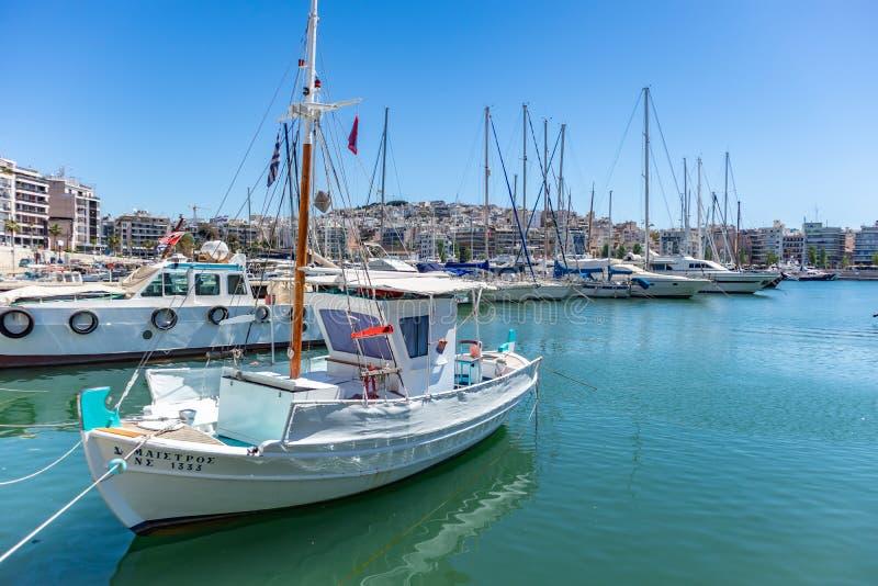 Marina Zeas in Piraeus, Griekenland Witte vastgelegde vissen-boot en jachten met masten Blauwe kalme overzeese, stads en hemelach royalty-vrije stock afbeelding