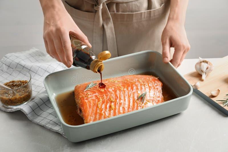 Marinade de versement de femme sur les saumons crus photos stock