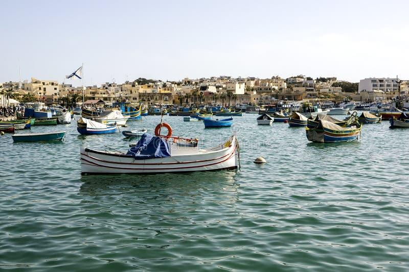 Marinaio con delle le barche dipinte colorate multi contro fondo delle casette basse immagine stock