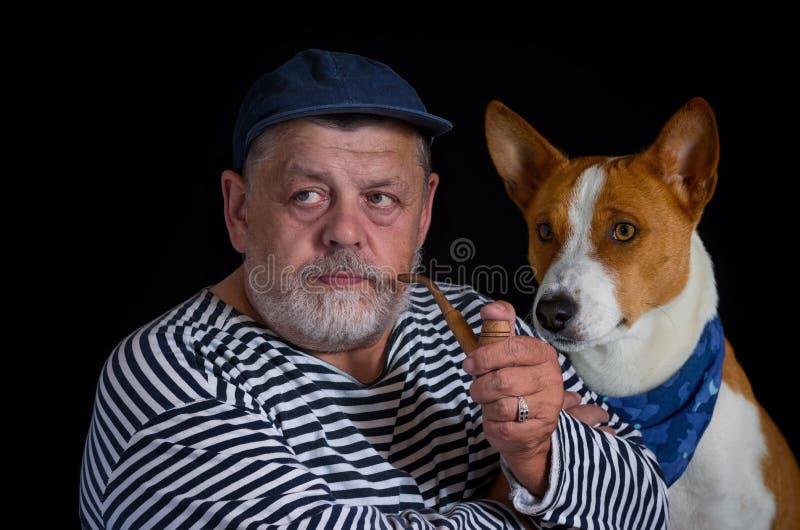 Marinaio pensionato ed il suo cane sveglio immagine stock libera da diritti