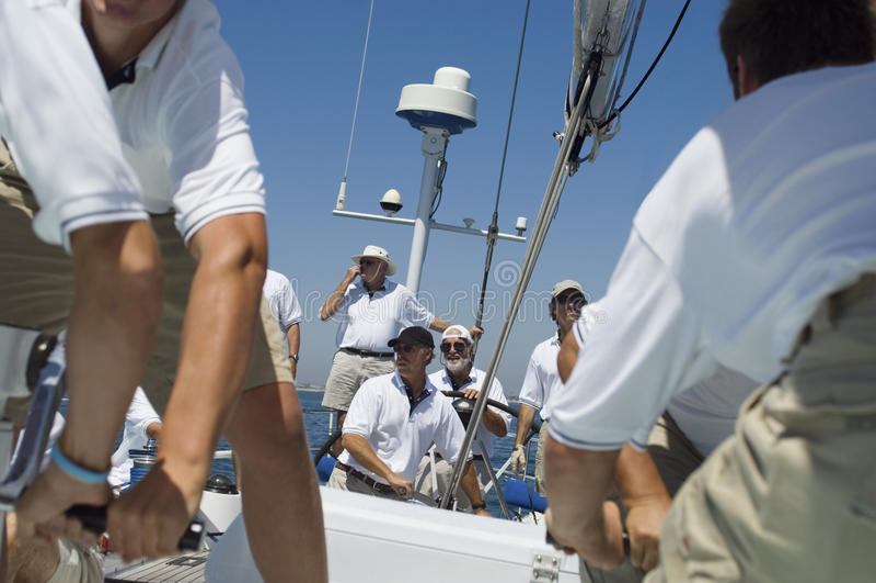 Marinaio sorridente With Crew On la piattaforma della barca a vela fotografia stock libera da diritti