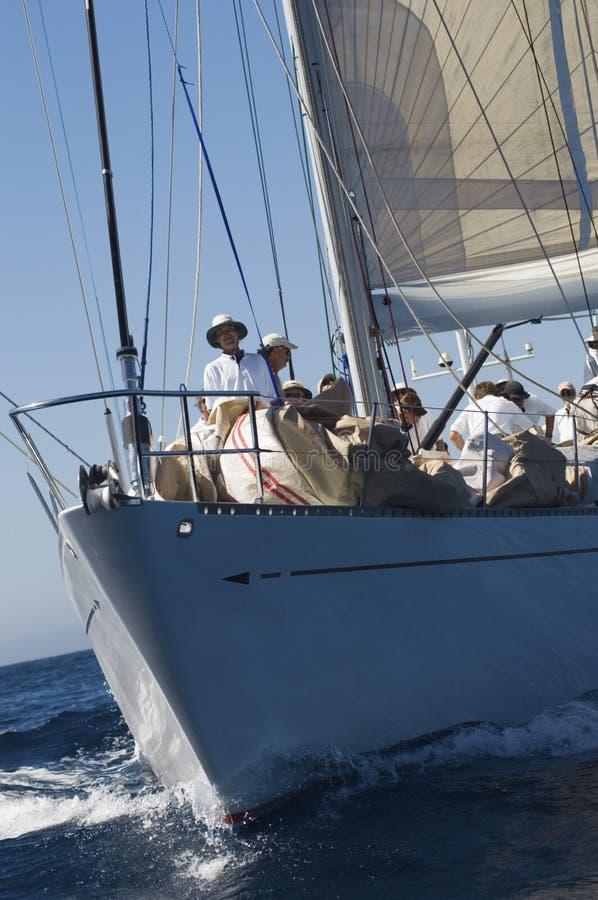 Marinaio sorridente With Crew On la piattaforma della barca a vela immagine stock libera da diritti