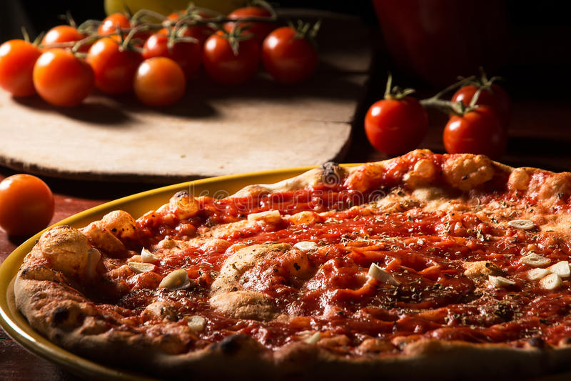 Marinara da pizza com alho e tomates na pá de madeira fotografia de stock royalty free