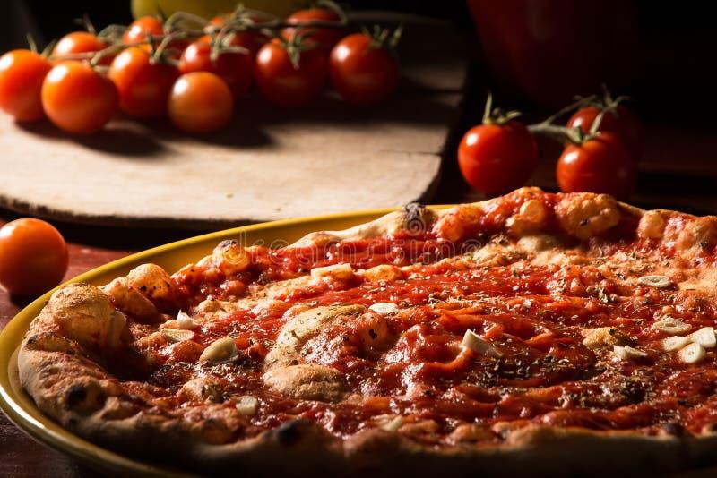 Marinara de la pizza con ajo y tomates en la paleta de madera fotografía de archivo libre de regalías