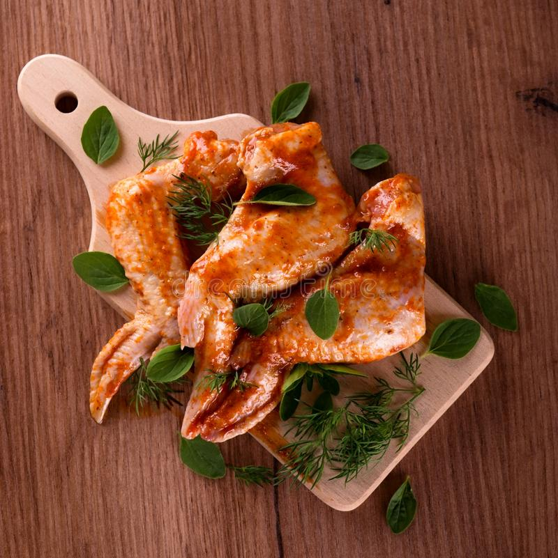 Marinated крыла цыпленка на деревянной доске с травами стоковое фото
