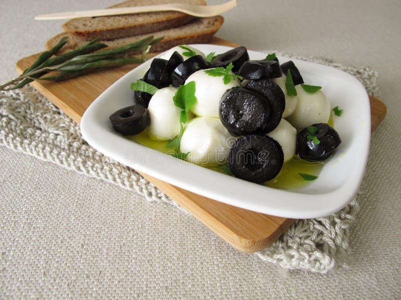 Marinated моццарелла с черными оливками, оливковым маслом и листьями мустарда стоковое изображение rf