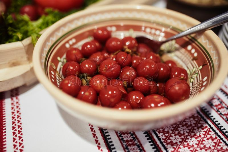 Marinated cherry tomatoes in a clay bowl on the table with embroidered towel. Close-up. Selective focus.  royalty free stock image
