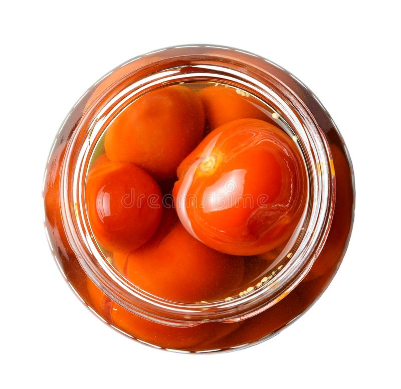 Marinated cherry tomatoes in a glass jar. View from above. White isolated background. Close up stock image