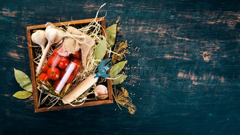 Marinated cherry tomatoes in a jar. Stocks of food. Top view. On a wooden background. Copy space stock photos
