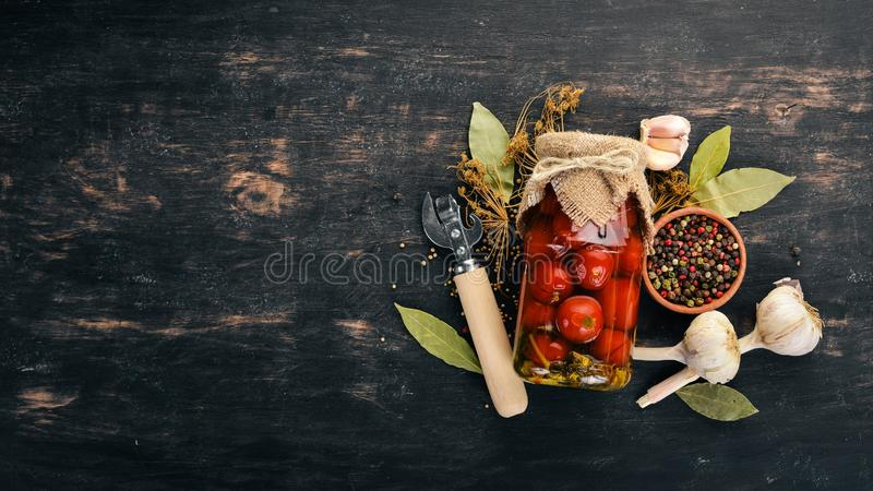 Marinated cherry tomatoes in a jar. Stocks of food. Top view. On a wooden background. Copy space royalty free stock photo