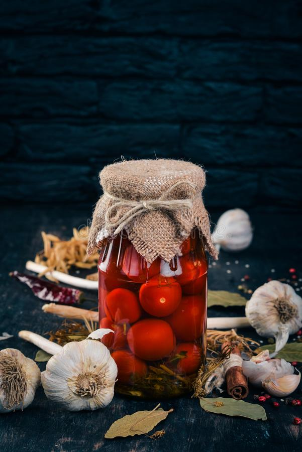 Marinated cherry tomatoes in a jar. Stocks of food. Top view. On a wooden background. Copy space stock photo