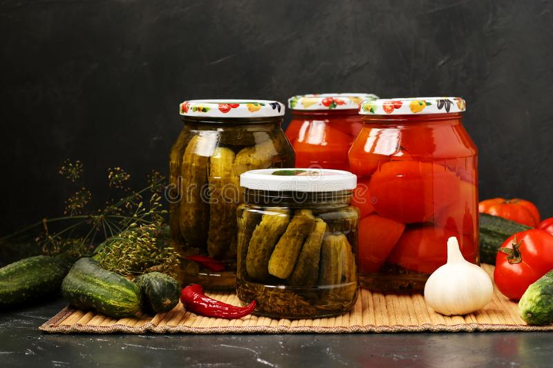 Marinated cucumbers and tomatoes in jars are located on a table, on a dark background. Fresh vegetables are randomly placed on the table. Harvest for the royalty free stock images