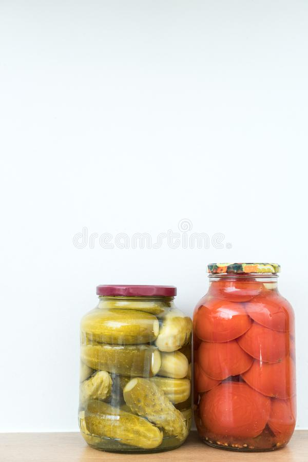 Marinated cucumbers and tomatoes. In jars. Space for text royalty free stock photo