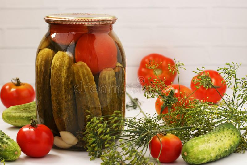 Marinated cucumbers with tomatoes are located in glass jar on a white background. On the table there are fresh tomatoes, cucumbers, dill branches. Free place stock photography