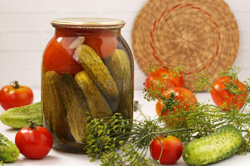 Marinated cucumbers with tomatoes are located in glass jar on a white background. On the table there are fresh tomatoes, cucumbers, dill branches. Harvest for royalty free stock images
