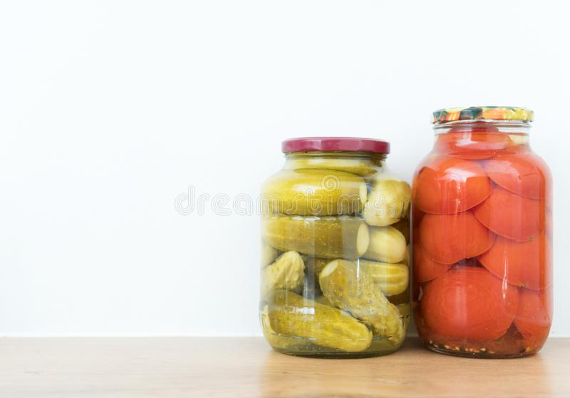 Marinated cucumbers and tomatoes. In jars. Space for text royalty free stock image