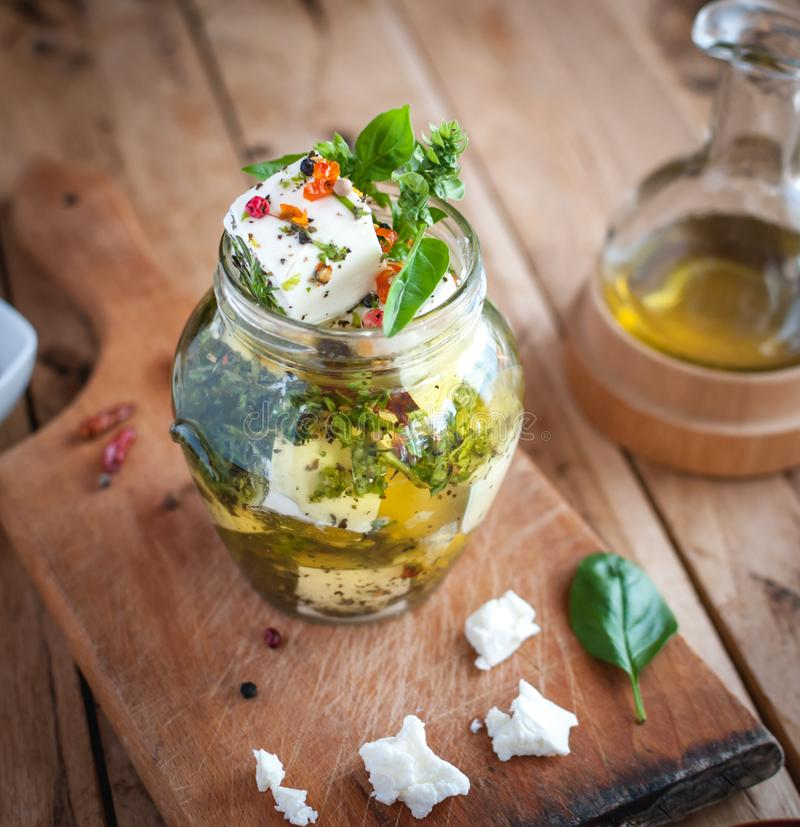 Marinated feta cheese in olive oil, herbs and red pepper flakes on wooden background royalty free stock image
