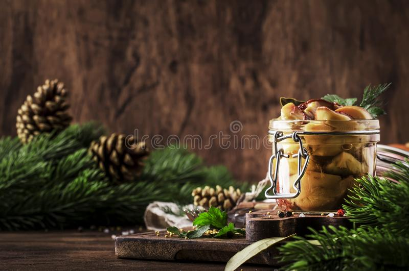 Marinated forest white mushrooms boletus in glass jar with spices and herbs, ready to eat, cooking food or canning concept, wooden royalty free stock photos