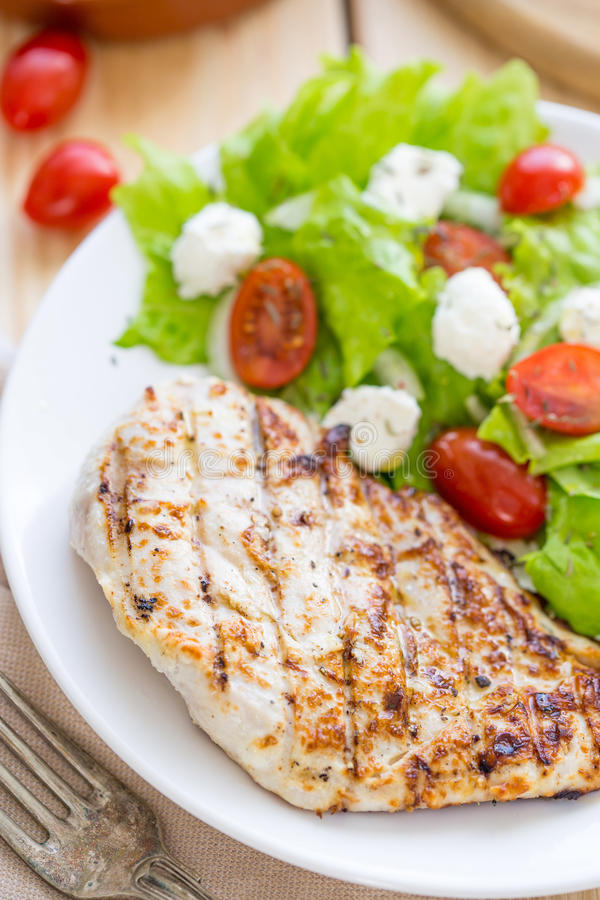 Marinated Grilled Healthy Chicken Breast served with Fresh Salad. Vertical View stock photo