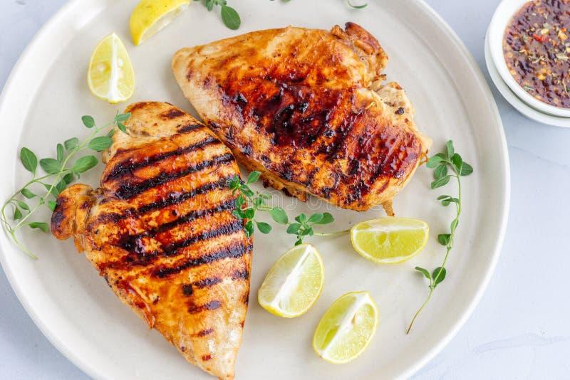 Marinated grillte gesunde Hühnerbrüste in einer weißen Platte und diente mit frischem Oregano auf weißem Hintergrund stockbild