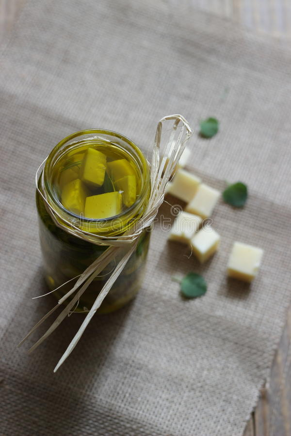 Marinated hard cow cheese in olive oil. Marinated hard cow cheese infused with green Dalmatian olives in olive oil and aromatic herbs stock photo