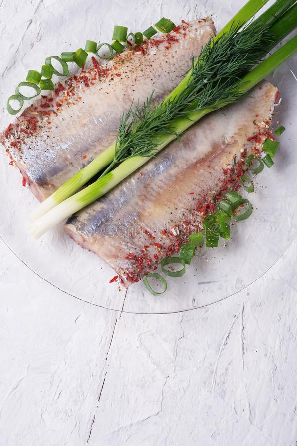Marinated herring fillet on a transporant plate with green onion and seasonings. served in Scandinavian style. Typical cooking stock photos