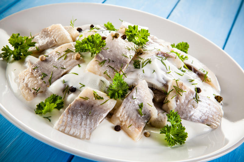 Marinated herring fillets. On wooden background stock photography