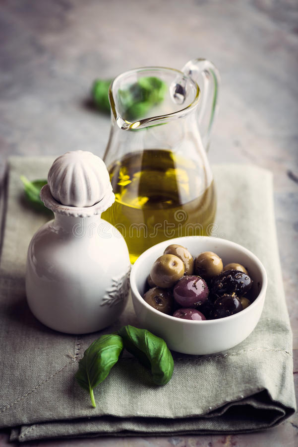 Marinated Olives and Olive Oil. Still life with marinated olives with herbs and olive oil in a glass jug royalty free stock image