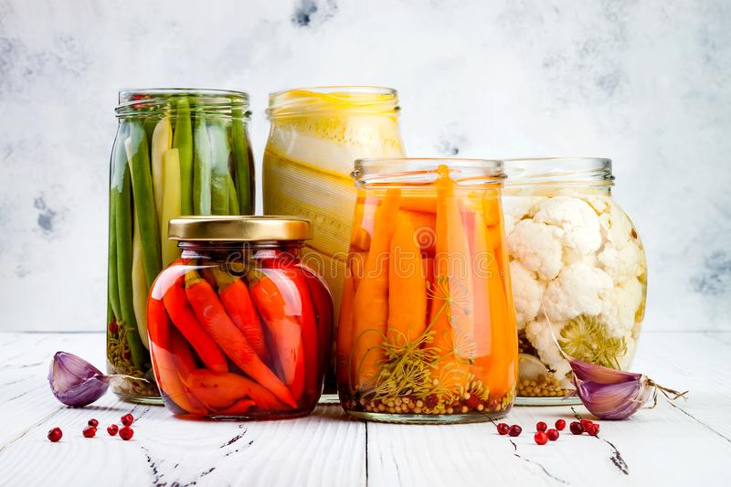 Marinated pickles variety preserving jars. Homemade green beans, squash, cauliflower, carrots, red chili peppers pickles. royalty free stock photo