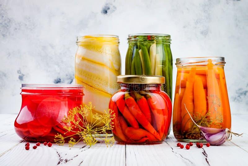 Marinated pickles variety preserving jars. Homemade green beans, squash, radish, carrots, cauliflower pickles. Fermented food. Marinated pickles variety royalty free stock image