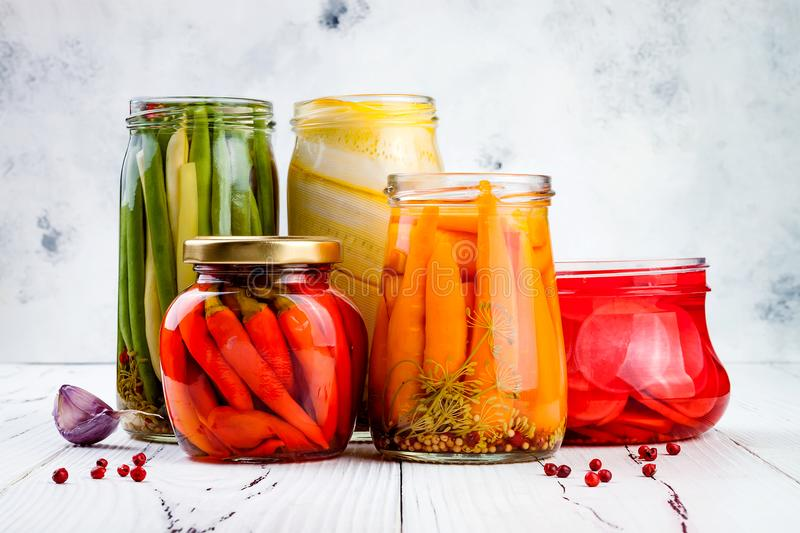 Marinated pickles variety preserving jars. Homemade green beans, squash, radish, carrots, red chili peppers pickles. royalty free stock photos