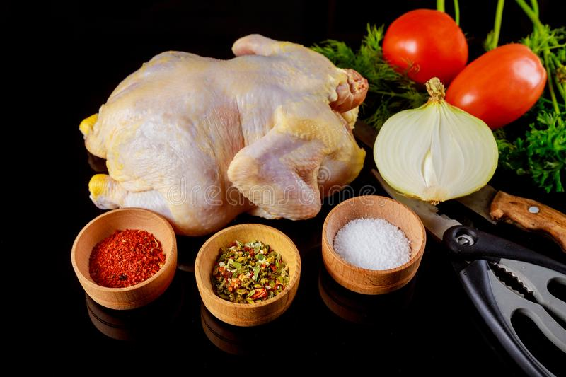 marinated raw chicken on a dark background. Raw chicken and vegetables royalty free stock photo