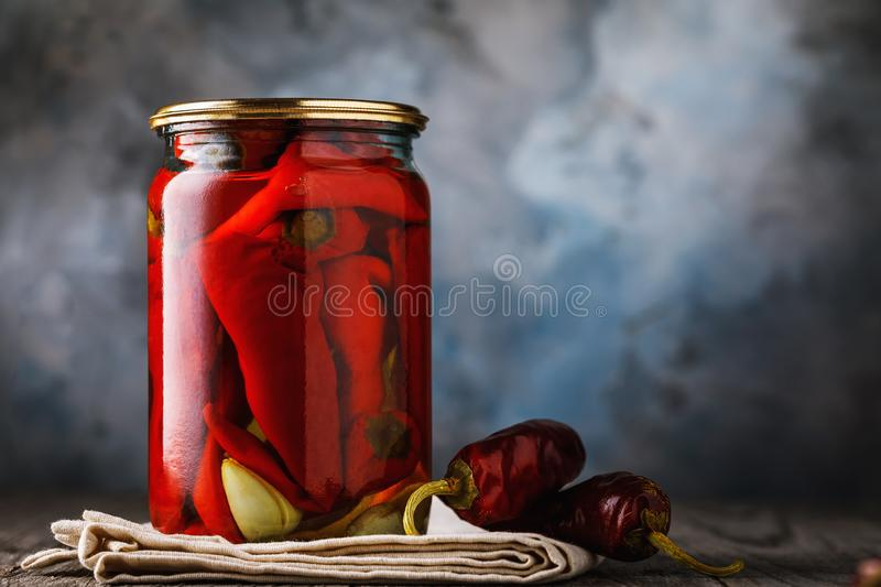 Marinated red pepper with garlic in a glass jar on a wooden table royalty free stock image