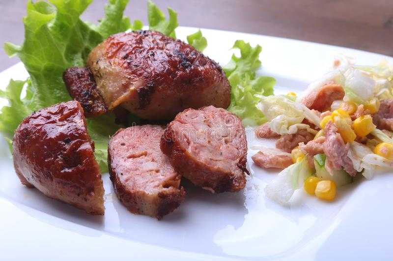 Marinated roaste chicken breasts cooked on BBQ and served with fresh salad on white plate, close-up. royalty free stock photo