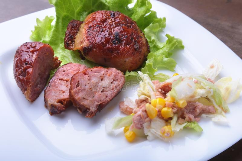 Marinated roaste chicken breasts cooked on BBQ and served with fresh salad on white plate, close-up. stock photography